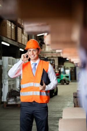 Male Supervisor Using Cell Phone At Warehouse photo