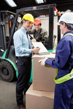 Supervisor Showing Clipboard To Foreman Stock Photo - 16489832