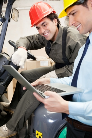 Supervisor And Forklift Driver Using Laptop photo