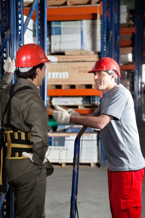 Foreman Communicating With Coworker At Warehouse photo