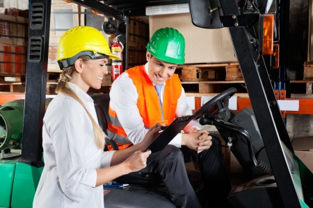 Supervisor Showing Clipboard To Colleague Sitting In Forklift photo