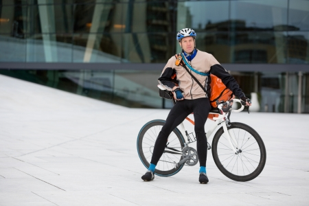Male Cyclist With Courier Bag Sitting On Bicycle photo