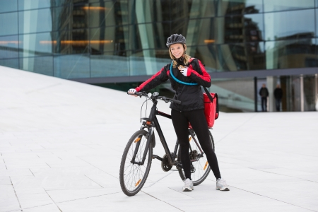 Female Cyclist With Courier Delivery Bag Using Walkie-Talkie photo