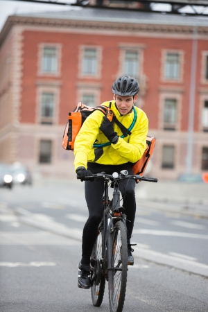 Male Cyclist With Courier Bag Using Walkie-Talkie Stock Photo - 16492619