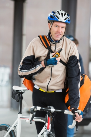 Male Cyclist With Courier Bag Using Walkie-Talkie Stock Photo - 16492531