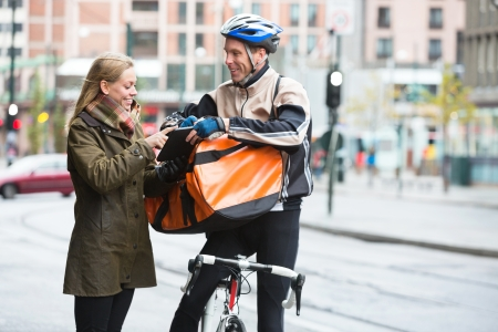 Courier Delivery Man Showing Digital Tablet To Young Woman Stock Photo - 16492534