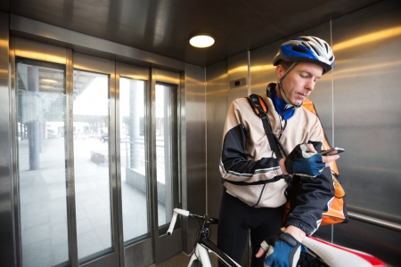Male Cyclist With Courier Bag Using Mobile Phone In An Elevator photo