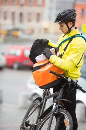 Young Male Cyclist Putting Package In Courier Bag Stock Photo - 16487198