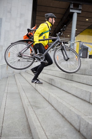 Courier Delivery Man With Bicycle And Backpack Walking Up Steps photo