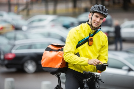 Male Cyclist With Courier Bag Using Mobile Phone On Street Stock Photo - 16489835