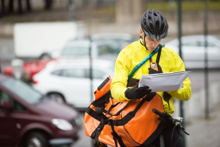 Male Cyclist With Package And Courier Bag On Street photo