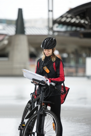 Female Cyclist With Courier Bag And Package On Street Stock Photo - 16492529