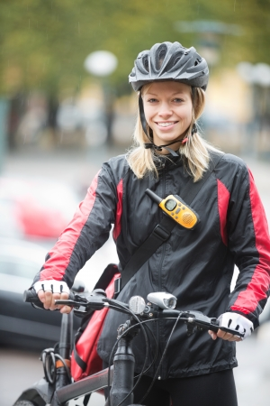 Young Female Cyclist With Courier Delivery Bag photo