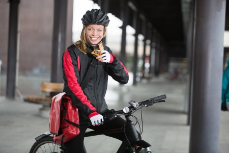 Female Cyclist With Courier Bag Using Walkie-Talkie Stock Photo - 16489833