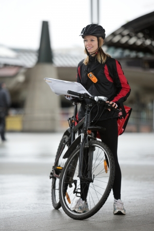 Female Cyclist With Courier Bag And Package On Street Stock Photo - 16492530