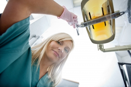 Female Dentist Adjusting Electric Light At Clinic photo