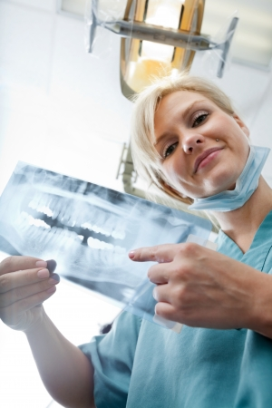 hygienist: Female Dentist Showing X-Ray Image At Clinic Stock Photo