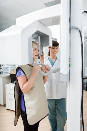 x ray equipment: Female Dentist With Patient Getting Her Teeth X-Rayed At Clinic Stock Photo
