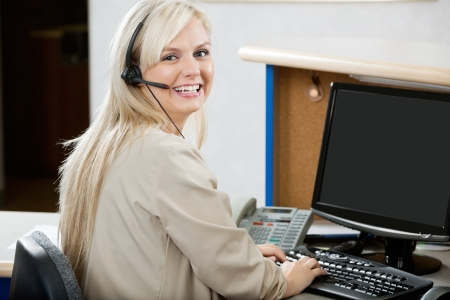 business reception: Cheerful Woman Using Computer At Reception Desk