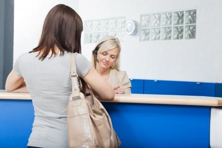 recepcion: Mujer joven con la recepcionista en Consultorio dental s Foto de archivo