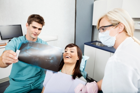 hygienist: Dentist With Female Assistant Showing X-Ray Image To Patient Stock Photo