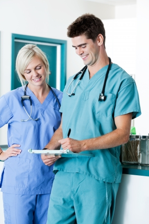 Male Doctor Writing On Clipboard With Colleague At Clinic Stock Photo - 16661016