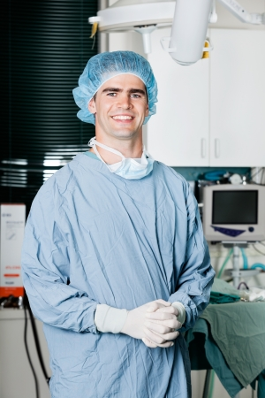 Cheerful Male Surgeon With Hands Clasped photo