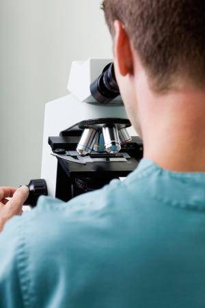 Male Researcher Using Microscope In Laboratory photo