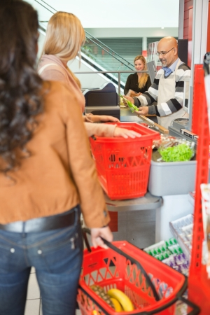 Customers Standing In Line At Checkout Counter In Supermarket photo