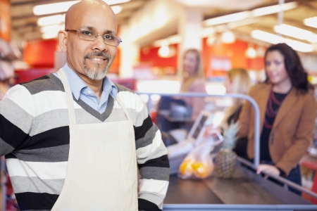 business owner: Grocery Store Cashier Standing At Checkout Counter Stock Photo