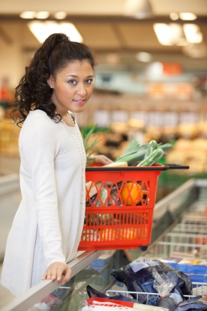 Woman With Shopping Basket Standing At Checkout Counter In Super Stock Photo - 16660940