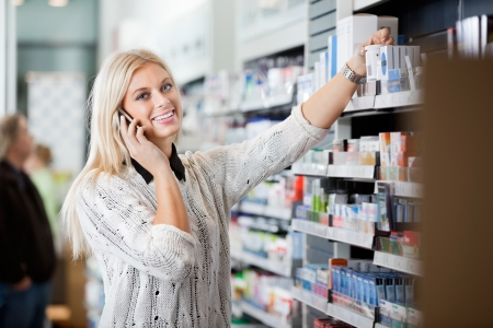 Young Woman Using Mobile Phone In Pharmacy photo