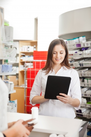Pharmacist Helping Customer with Digital Tablet photo