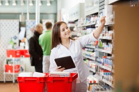 drugstore: Mujer sonriente que usa la tableta digital para las compras en el supermercado