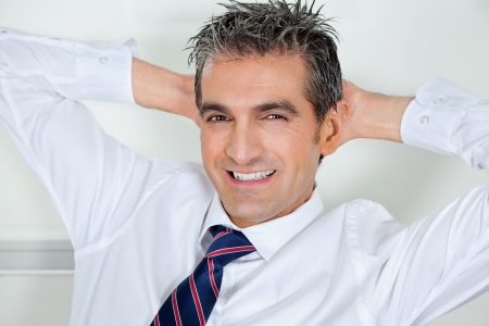 Mid Adult Businessman Relaxing With Hands Behind Head Stock Photo - 16672676