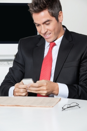 Businessman Using Cell Phone At Desk photo