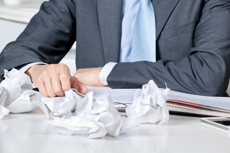 Businessman Sitting At Desk With Crumpled Papers Stock Photo - 16672678