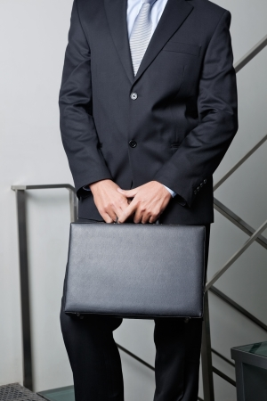 Midsection Of Young Businessman Carrying Briefcase photo