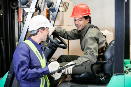 warehouse equipment: Forklift Driver Communicating With Supervisor