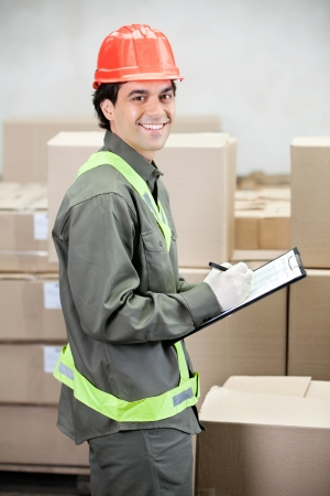 Supervisor Writing Notes At Warehouse photo