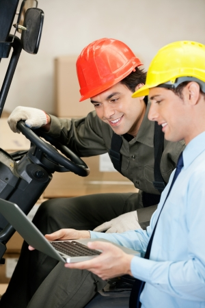 Male Supervisor And Forklift Driver Using Laptop photo