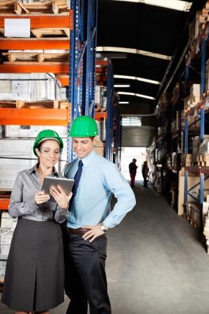 foreman: Supervisors Using Digital Tablet At Warehouse Stock Photo