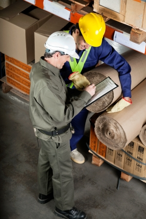 safety check: Foreman With Supervisor Writing Notes At Warehouse