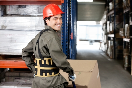 Warehouse Worker Pushing Handtruck With Cardboard Boxes photo