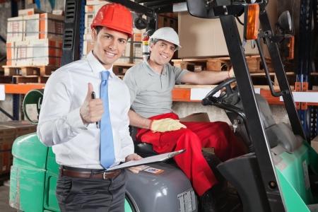Supervisor Gesturing Thumbs Up At Warehouse photo