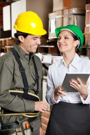 Supervisor With Digital Tablet And Foreman At Warehouse photo