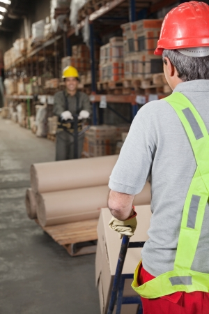 Warehouse Workers Pushing Handtruck Stock Photo - 16672701