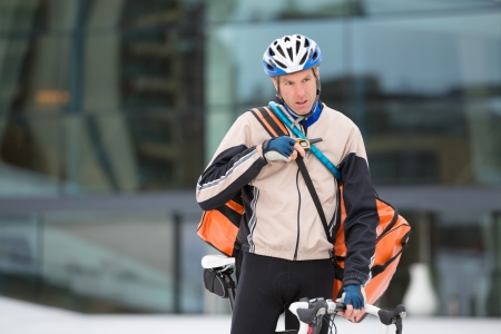 Young Courier Delivery Man With Bicycle Using Walkie-Talkie photo