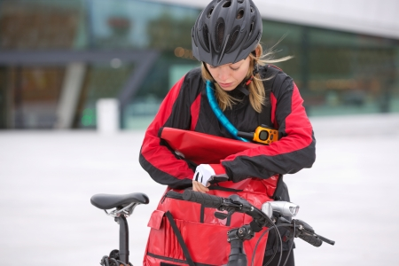 Female Cyclist Looking Through Courier Delivery Bag photo