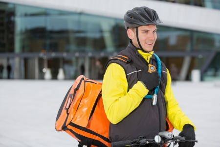 Male Cyclist With Courier Delivery Bag Using Walkie-Talkie photo